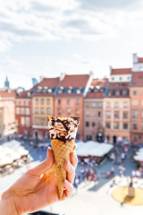 Hand holding one white vanilla chocolate ice cream gelato cone with vertical background of Warsaw,...