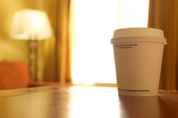Early morning cup of coffee is placed on desk in hotel room