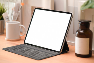 Mockup lank screen modern tablet and poster on a white workspace desk