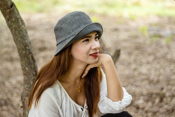 Women white skin lovely brown hair wearing a gray hat red lip wear white shirt wearing black pants women sit poses photography portrait under the tree In the garden.