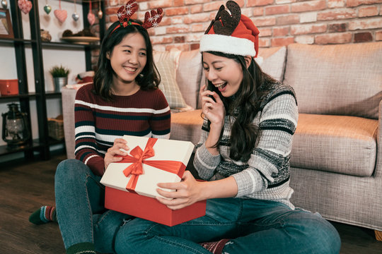 Group of two asian girls celebrating Merry Christmas and Happy Holidays concept. sisters exchanging present sending opening gift box at home. Friends are interested amazed and surprised on boxing day