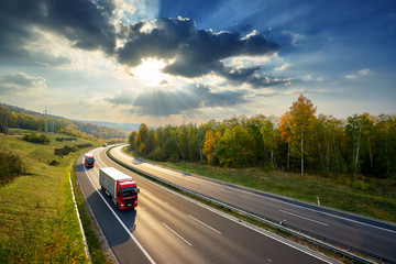 Three red trucks driving on the asphalt highway between deciduous forest in autumn colors under the rays of the sunset and dramatic clouds. View from above.