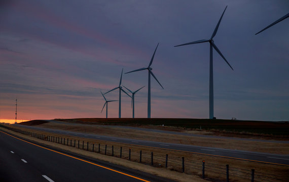 Wind energy blows into West Texas wind turbine farms in the colorful sunset showing renewable energy works
