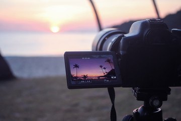 The camera with flip screen  while recording a video view of the sunrise on the beach