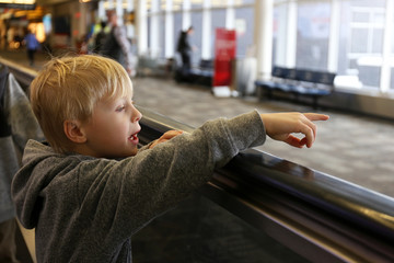 Little Kid on People Mover at Airport Pointing out Window