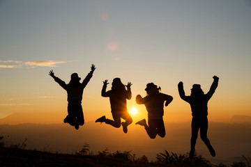 Group of happy young people jumping on the hill. Young women enjoying on their holiday outdoors.
