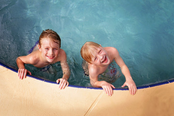 Happy Little Kids Smiling as They Swim in the Family Swimming Pool