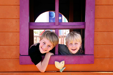 Happy Little Kids Smiling at the Park as they Peek out the Window of a Clubhouse Fort
