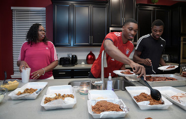American track and field sprinters Noah Lyles (R) and his brother Josephus share a dinner with their mother, Keisha Caine, at their home after training at the National Training Center in Clermont, Florida