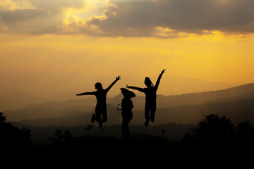 Group of happy people jumping in the mountain at sunset, concept about having fun on the hill, silhouette
