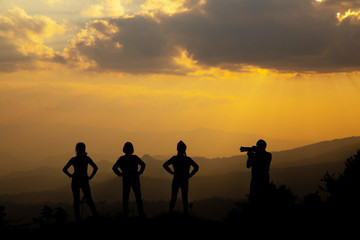 Group of happy people photographing in the mountain at sunset, concept about having fun on the hill, silhouette