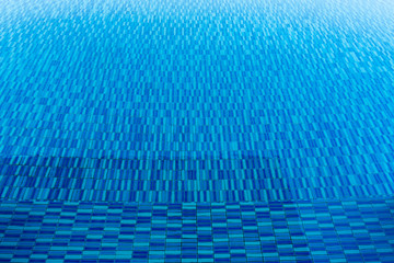 Blue water texture in swimming pool. Travel and summer background concept.