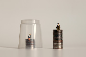 A glass ceiling concept. A miniature man and a miniature woman sitting on a pile of coins of different heights.