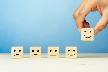 Customer service evaluation and satisfaction survey concepts. The client's hand picked the happy face smile face symbol on wooden cube, copy space