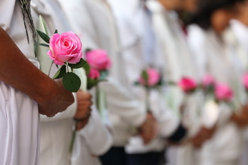 group of people offering rose flower expressing the condolence for respecting the lost of love one during mourning ceremony in funeral