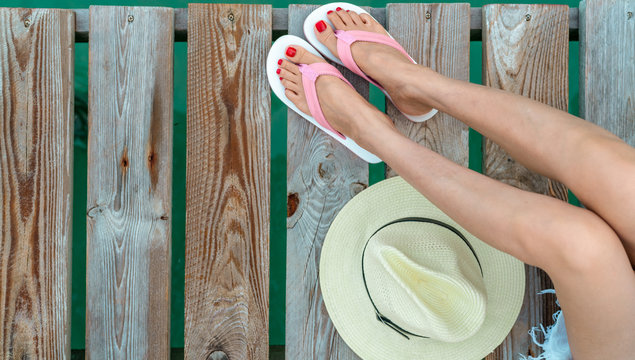 Young Asian woman with red pedicure wearing pink and white sandals sit on wooden bridge and put hat beside legs on holiday. Summer vacation. Summer vibes. Woman travel alone. Happy backpacker girl.