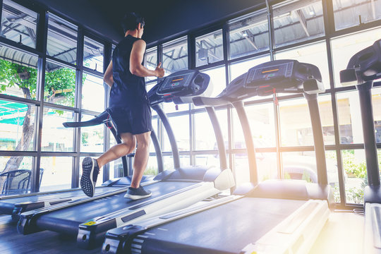 Fit man running in machine treadmill at fitness gym