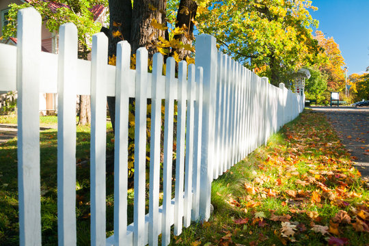 Beautiful colorful autumn scene with white fence and fall colors in Finland.