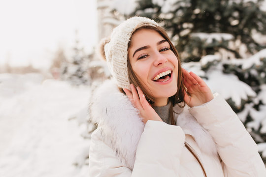 True brightful emotions of winter girl in knittted hat smiling to camera on street full with snow. Closeup portrait, enjoying snow, waiting for christmas, cheerful mood, happiness