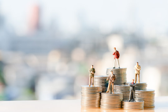 Miniature people: Small businessmen standing on coin stacks with city background. Step, Money, Financial, Business Growth concept.