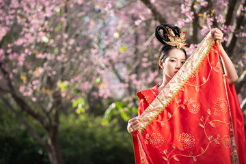 space beautiful Chinese young woman wearing red traditional cheongsam in cherry blossoms garden Fototapete