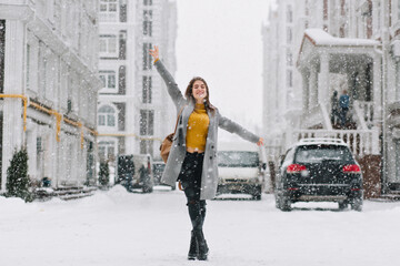 Full-length portrait of inspired female model in stylish coat posing with pleasure in winter city. Outdoor photo of glad blonde woman enjoying snowfall during walk around town.