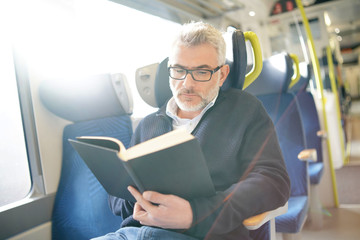 Mature man reading book while traveling on a train