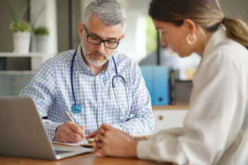 Patient having medical appointment with practitioner in doctor's office