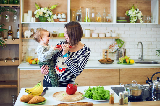 Happy young woman holding a 1 year old child and cooking together in the kitchen