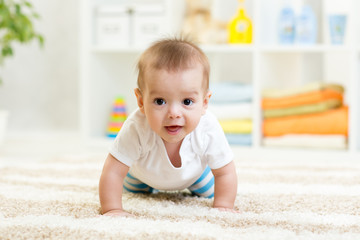 Nursery baby boy crawling on floor indoors at home