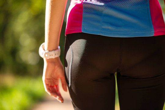 Photo from back buttocks of sporty woman in park on summer.