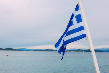flag of Greece on the ship against the cloudy sky