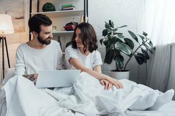 beautiful young couple in pajamas lying in bed, using laptop and looking at each other