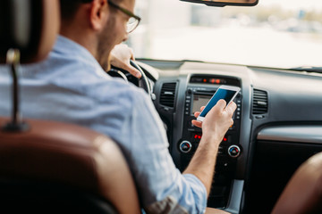 Man looking at mobile phone while driving