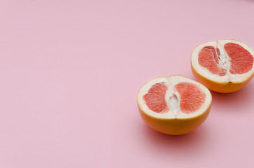 Sliced ripe and fresh grapefruit on pink background.Sweet colors