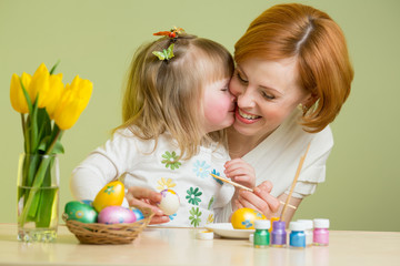 Little child girl with her mother coloring Easter eggs
