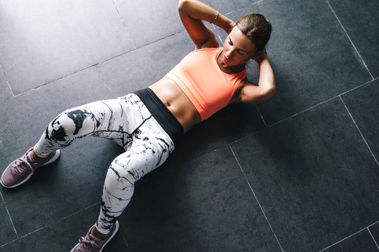 Model wearing fashion sports wear doing exercise at black floor
