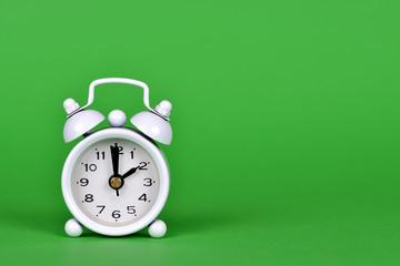 White alarm clock on green background.