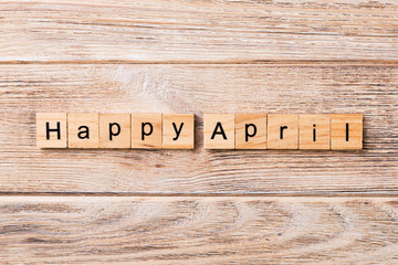 Happy april word written on wood block. Happy april text on table, concept