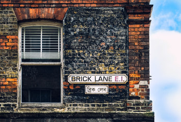 Brick lane vinrage street sign with house window and red brick wall