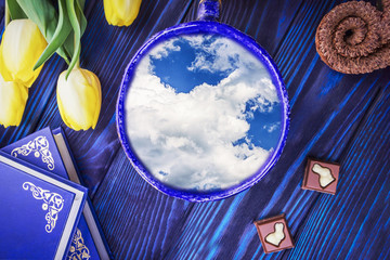 Cup with sky inside, books and spring yellow tulips on a blue background. Concept better weather forecast for spring and Easter