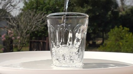 Fototapete - Pouring fresh water to a clean glass on a white plate in natural background in Slow Motion