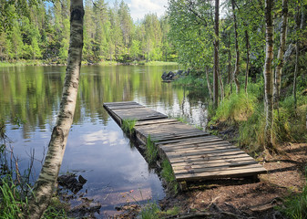 Landscape with a dock or a pier on the lake on a sunny summer day. Oulanka National Park, Kuusamo, Finland. Wild calm nature of the North for recreation and fishing.