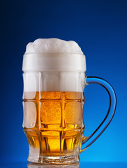 Faceted mug of light beer with foam on blue background