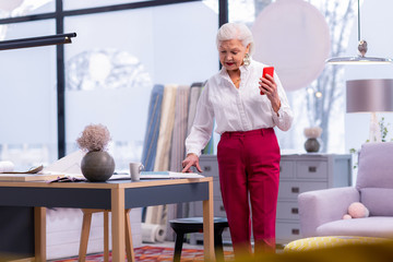 Elderly fancy businesswoman standing in the office holding a phone