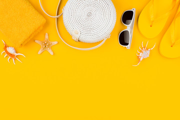 White handbag with beach accessories on yellow background, copy space