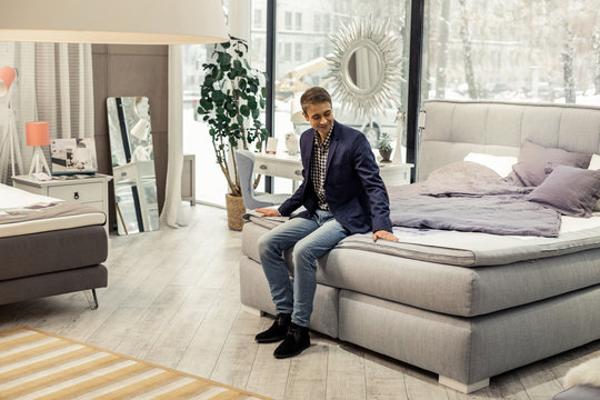 Good-appealing beaming man resting on new bed in furniture store