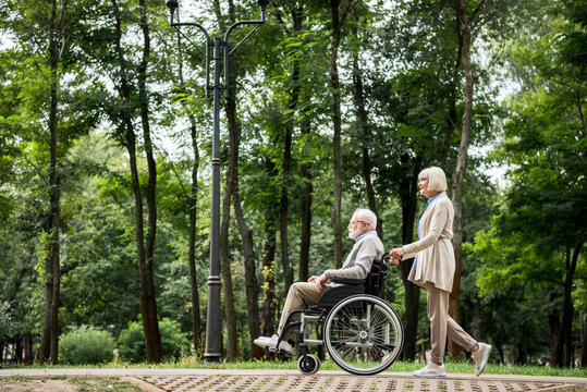 senior woman carrying husband in wheelchair while walking in park