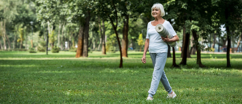 happy senior woman walking in park and holding fitness mat