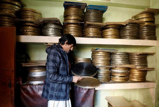 A worker checks a movie reel box at a cinema house in Peshawar